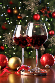 Glasses of red wine in front of Christmas tree