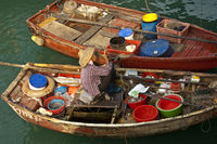 Female fish monger with hat on her boat,Hong Kong