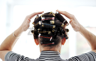 Woman with curlers on hair