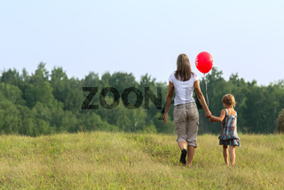 Young mother with the child goes across the field. Outdor.