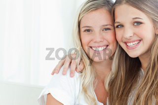 A smiling pair of sisters looking at the camera