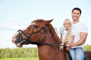 Little girl with her father on a horse