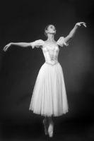 Beautiful dancer posing in a white dress, on studi