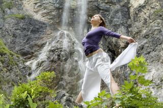 Junge Frau trainiert Übungen vor einem Wasserfall