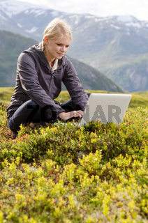 junge blone Frau sitzt mit Laptop in Bergwiese