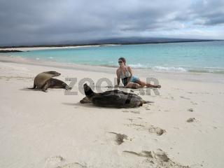Woman tourist lays among seals on beach