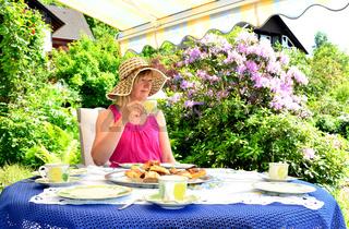 Frau trinkt Kaffee auf der Terrasse