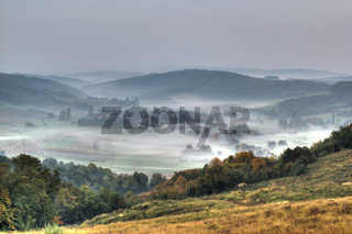 Rural mountain village in fog aerial view