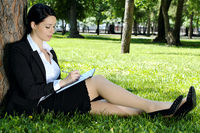 Businesswoman writing something to diary