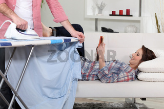 Woman lying on the couch reading while her boyfriend does the housework