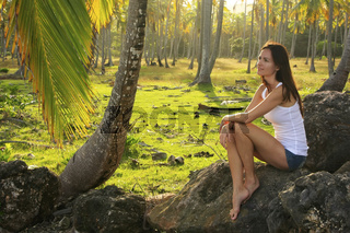 Young woman sitting on rocks in coconut trees grove, Las Galeras beach