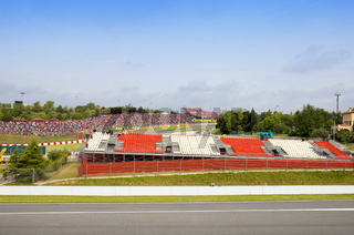 BARCELONA- MAY 9: Spectators on grass and empty tribunes - before opening race Porsche Mobil 1 Supercup  on autodrome 'Catalunya Montmello' on may 9