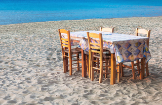Greek taverna table and chairs on sandy beach