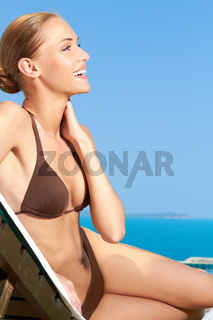 Cute woman sitting on sunbed and smiling