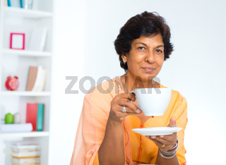 Mature Indian woman drinking coffee
