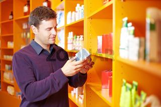 Mann betrachtet Produkt in Apotheke