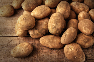 Fresh potatoes on wooden background