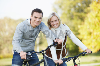Attractive couple on bicycles in the park