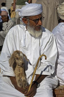 Omani man with a goatling at the goat market,Nizwa