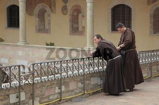 Mönche im Kreuzgang des Kloster San Francesco in Assisi