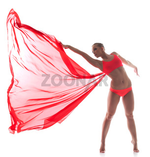Flexible dancer posing with red cloth in studio