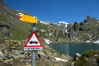 Warnschild vor Autoverkehr inmitten der Walliser Alpen