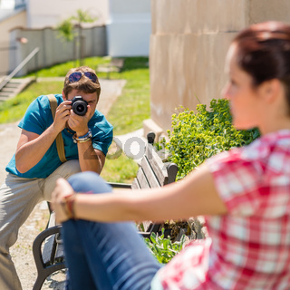 Man taking picture of woman on bench