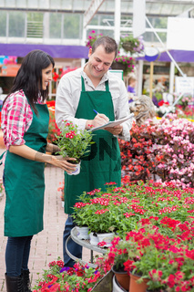 Two garden center employees making notes