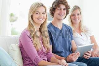 Three smiling people sit together on the couch with a tablet