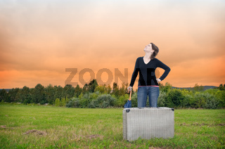 Young woman standing on a meadow with suitcase and umbrella