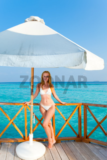 Young woman  on a water villa terrace