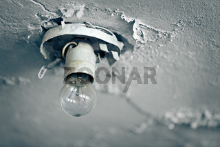 Old light bulb on ceiling of abandoned house
