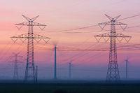 Strommasten und Windräder in der Abenddämmerung