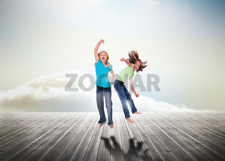 Sisters having fun jumping over wooden boards