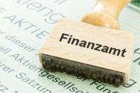 Stempel mit Aufschrift Finanzamt auf einer Aktie