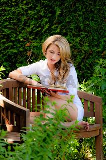 Frau beim Lesen eines Buches im Garten