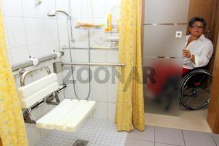 Frau im Rollstuhl in einem behindertengerechten Badezimmer