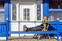 man sitting relaxed on the porch of his house