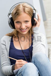 Young woman taking notes listening to music