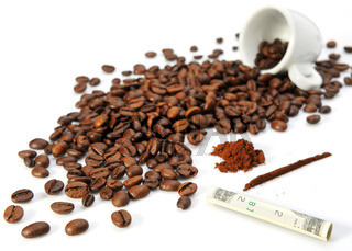 Coffee grains, a cup and twisted paper currency