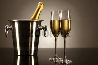 zwei gläser mit champagner mit einer flasche sekt in einem kühler