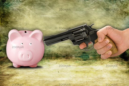 Piggy bank and hand with gun