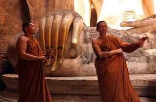 Moenche bestaunen die Buddha Figur  im Wat Si Chum Tempel in der Tempelanlage von Alt-Sukhothai in der Provinz Sukhothai im Norden von Thailand in Suedostasien.