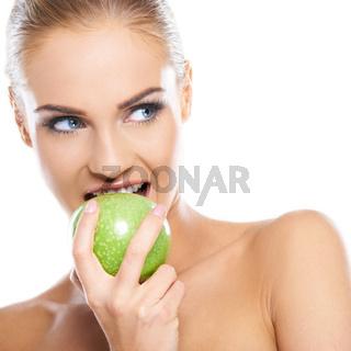 Woman tries to bite a fresh green apple