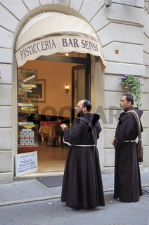 Mönche vor einer Bäckerei