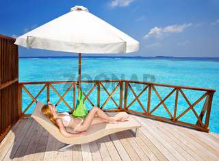 Young woman tans on a water villa terrace