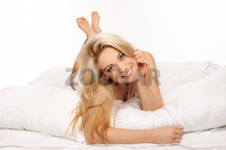 Happy blonde relaxing on a duvet
