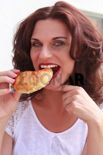 Lecker croissant mit einer hübschen Frau beim esse