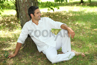 35 years old lying down under a tree