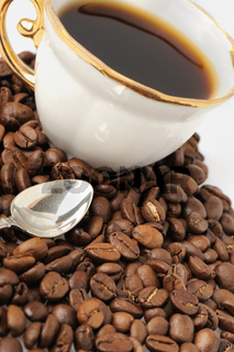 stylish coffee cup with silver spoon and seed